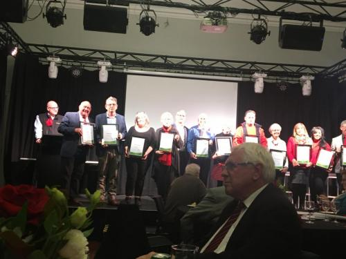 Whole group of 2021 recipients on stage. Strong lighting but William is clear!!IMG 1804